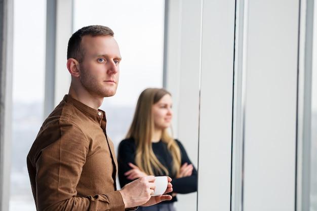 Elegante giovane coppia innamorata davanti a grandi finestre panoramiche. una giovane donna e un uomo sono in piedi davanti a una grande finestra con un caffè. messa a fuoco selettiva