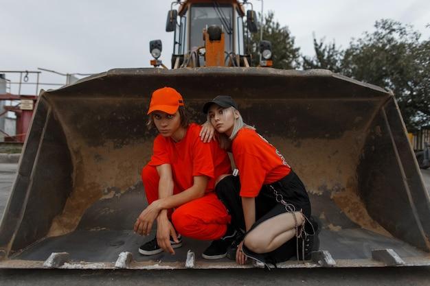 Elegante giovane coppia in abiti arancioni alla moda con cappuccio seduto in un secchio di un veicolo da costruzione