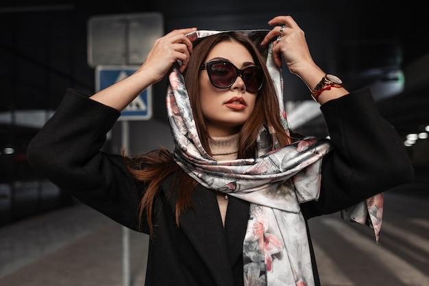 Elegante giovane donna europea con belle labbra sexy in occhiali da sole alla moda in cappotto mette elegante sciarpa di seta sulla testa in città. ragazza del modello di moda di affari del ritratto. signora di bellezza dell'annata sulla strada.