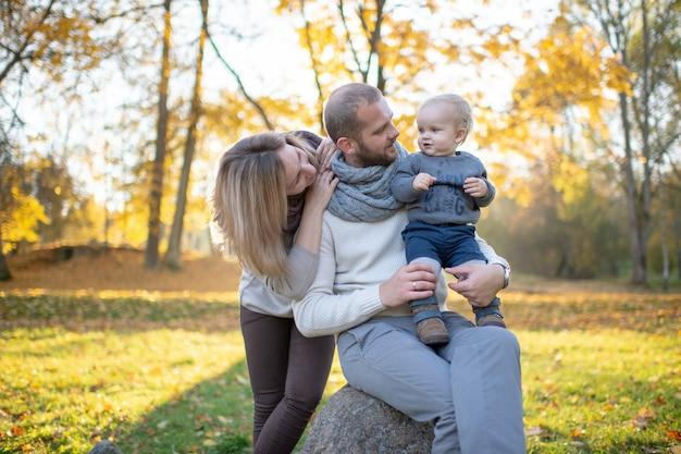 Elegante giovane famiglia con il loro bambino piccolo trascorrere del tempo nel parco
