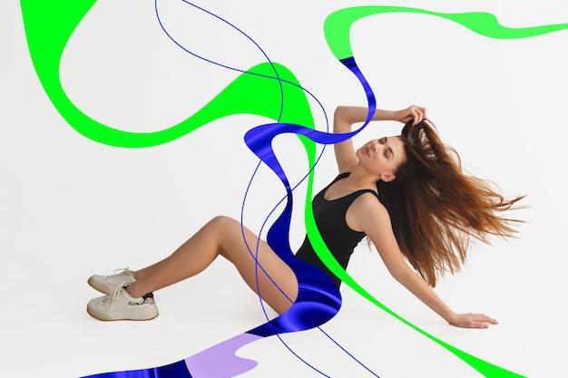 Elegante ritratto di giovane ragazza su sfondo bianco studio con luminose linee illustrate di fluidi colori neon. ballare, impazzire, divertirsi, alla moda. figura intera, opere d'arte, design.