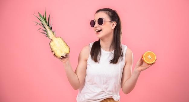 Ragazza alla moda in occhiali da sole sorride e tiene i frutti su una parete rosa. concetto di vacanza estiva.