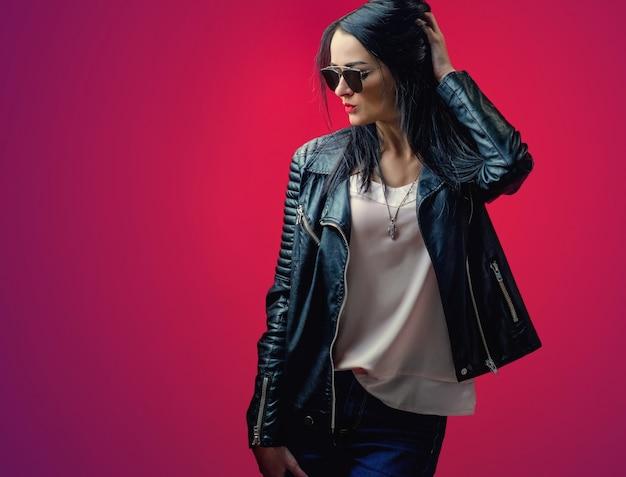 Elegante ragazza con i capelli neri in una giacca di pelle e occhiali da sole alla moda su una parete rosa brillante.