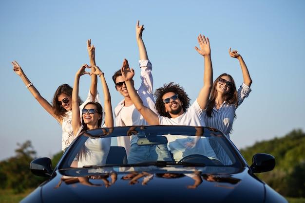 Eleganti ragazze e ragazzi in occhiali da sole sono seduti in una cabriolet nera sulla strada alzando le mani e sorridendo in una giornata di sole. .