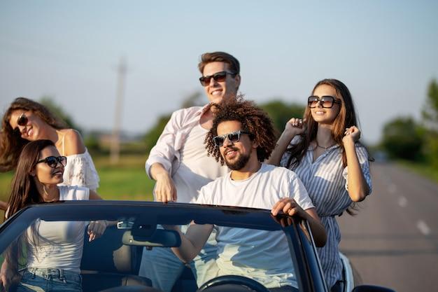 Eleganti ragazze e ragazzi in occhiali da sole vestiti con abiti bianchi sono seduti in una cabriolet nera in una giornata di sole. .