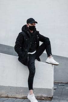 Elegante giovane ragazzo con una maschera protettiva nera in giacca nera, berretto, felpa con cappuccio e jeans con scarpe da ginnastica bianche si siede in città vicino al muro