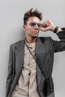 Elegante giovane bell'uomo con acconciatura e barba in abiti casual alla moda con blazer e camicia con borsa indossa occhiali da sole vicino al muro grigio in città