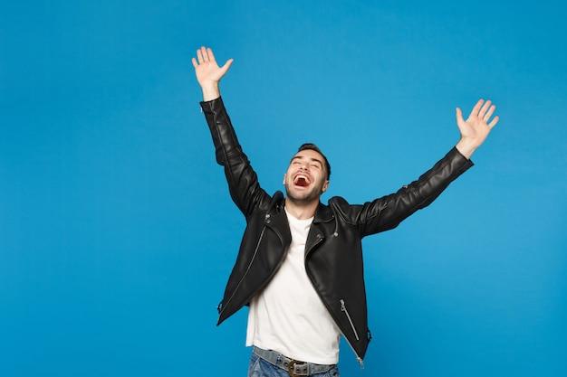 Elegante giovane uomo barbuto felice in giacca di pelle nera t-shirt bianca facendo gesto vincitore dire sì isolato su parete blu sfondo ritratto in studio. concetto di emozioni sincere della gente. mock up copia spazio