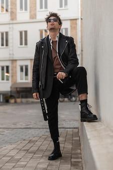 Elegante giovane hipster in occhiali da sole scuri alla moda in una giacca di pelle nera in jeans in stivali cool si alza e fuma vicino a un muro vintage. bel modello di moda ragazzo americano su una pausa fumo all'aperto