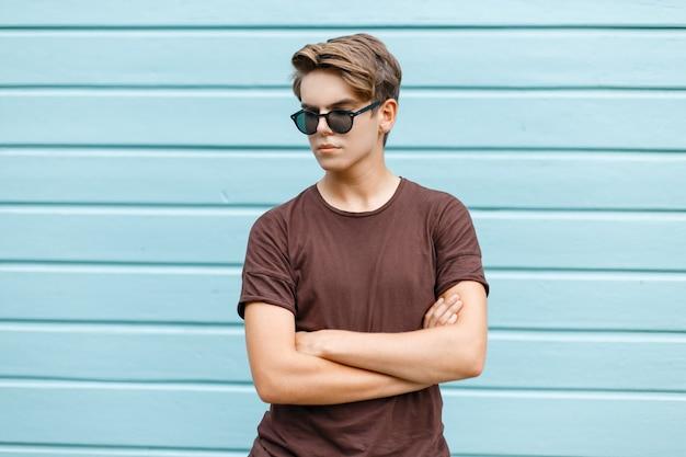 Uomo giovane alla moda hipster con un'acconciatura alla moda in occhiali da sole scuri in una maglietta marrone alla moda in posa vicino a una parete di legno blu in una calda giornata estiva di sole