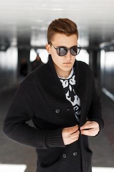 Giovane alla moda in maglione nero e occhiali da sole in una giornata di sole