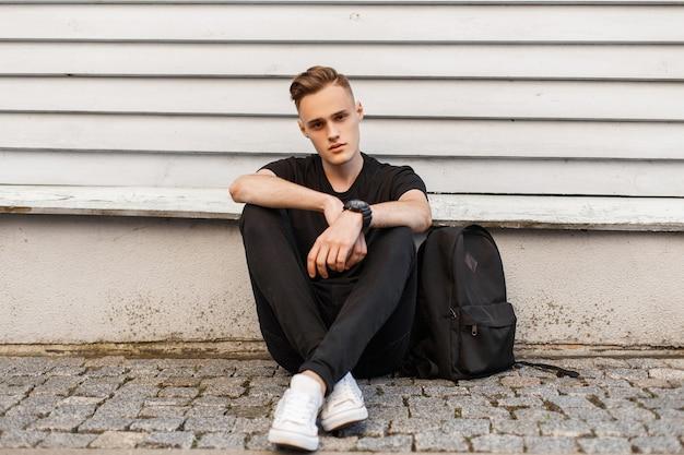 Giovane alla moda in una maglietta nera in jeans alla moda in scarpe da ginnastica bianche con uno zaino sportivo si siede vicino a un muro di legno vintage all'aperto