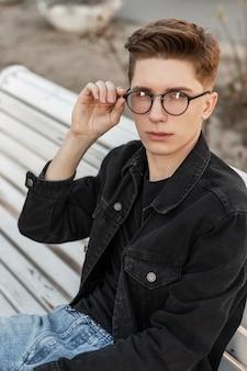 Il giovane alla moda in vestiti di jeans di moda raddrizza gli occhiali vintage in strada. fantastico modello di ragazzo europeo in abbigliamento casual alla moda e alla moda in posa su una panchina di legno bianca per strada stile casual