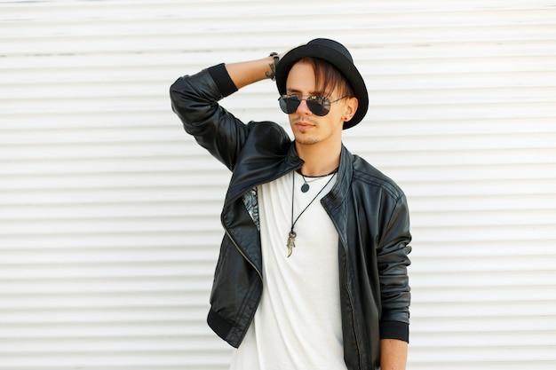 Giovane alla moda in occhiali da sole alla moda, cappello in giacca di pelle alla moda vicino a persiane in metallo bianco