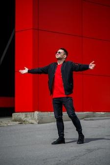 Giovane alla moda in una maglietta alla moda in occhiali da sole in jeans blu vintage in posa in una giornata di sole vicino all'edificio rosso all'aperto. ragazzo moderno per strada. stile giovanile