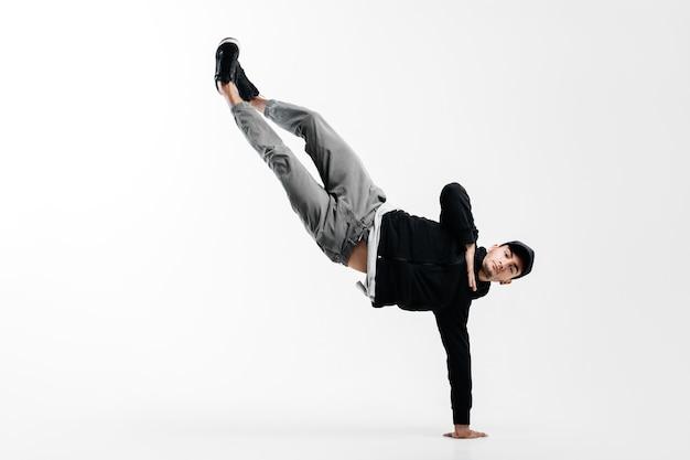 Il giovane alla moda sta ballando la breakdance. è in piedi su un braccio e solleva entrambe le gambe.