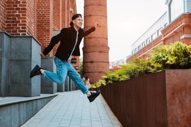 Un giovane alla moda in jeans e berretto fa un salto in città come se stesse correndo nell'aria. gioventù attiva allegra di un uomo. fricchettone.