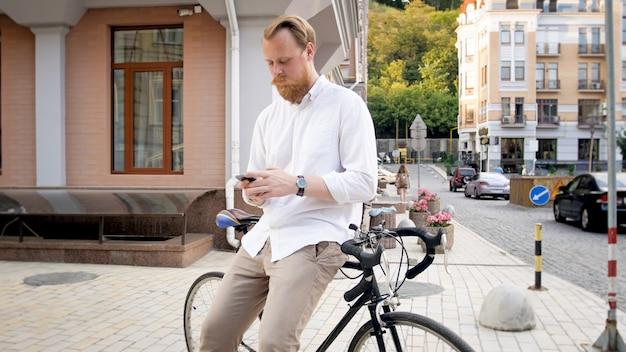 Giovane alla moda che si appoggia sulla bicicletta e digita il messaggio sullo smartphone.