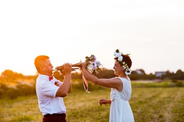 Giovane alla moda che gioca sul tubo per sua moglie sul campo
