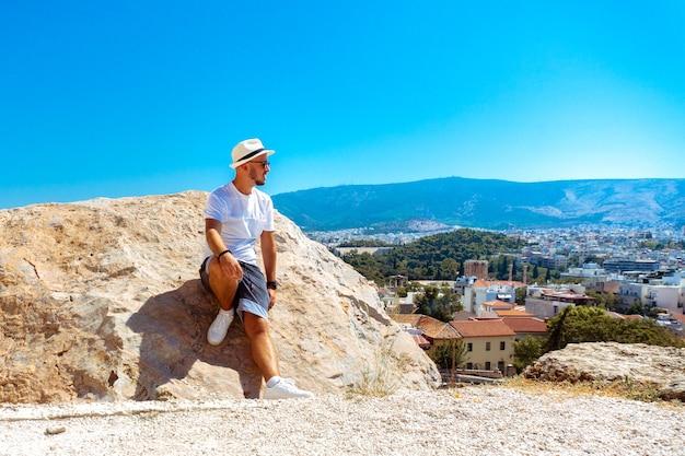 Elegante giovane uomo un occhiali da sole guarda la vista della città dall'alto collina