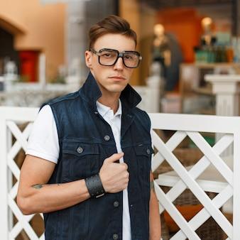 Elegante giovane uomo in occhiali vintage e un gilet di jeans cammina nel centro commerciale