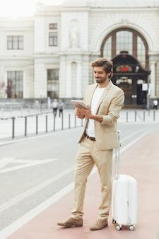 Elegante giovane uomo con la barba utilizzando la tavoletta digitale per lavorare stando in piedi sull'aria fresca con i bagagli