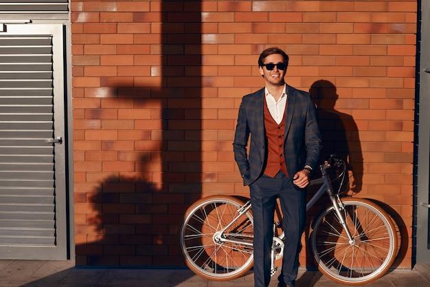 Elegante giovane uomo con la bicicletta in piedi sulla strada