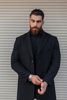 Giovane alla moda con una pettinatura e la barba in un cappotto nero alla moda in posa vicino a un muro di metallo