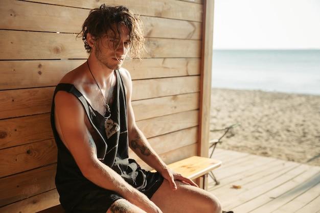 Elegante giovane uomo serio seduto alla capanna sulla spiaggia