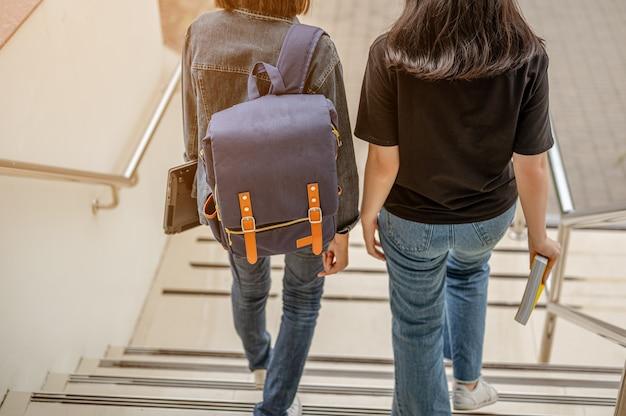 Giovani studenti alla moda che scendono sulle scale del corridoio del college libri di conoscenza ed educativi
