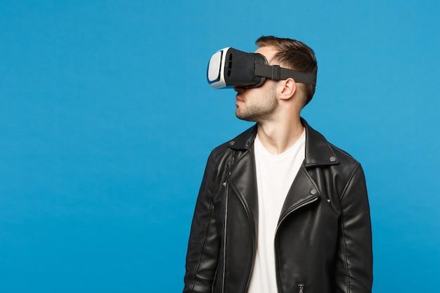 Elegante giovane uomo con la barba lunga in giacca nera t-shirt bianca guardando in cuffia, realtà virtuale vr isolato su parete blu sfondo ritratto in studio. concetto di stile di vita di emozioni di persone. mock up copia spazio.