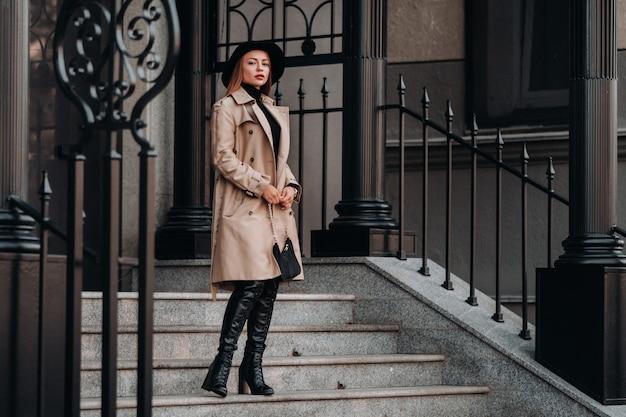 Elegante giovane donna in un cappotto beige in un cappello nero su una strada cittadina. moda di strada femminile. abbigliamento autunnale stile urbano.