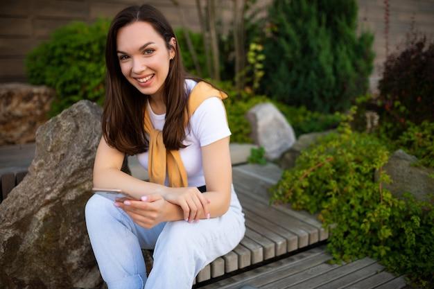 Giovane donna alla moda che gode del tempo libero che si siede nel parco verde di estate e che chiacchiera sul telefono.
