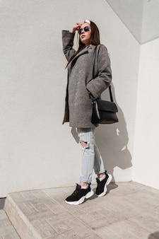 Elegante giovane donna in cappotto giovanile casual alla moda con borsa in scarpe da ginnastica con bandana in occhiali da sole sta riposando in una giornata di sole vicino al muro vintage sulla strada. attraente ragazza urbana e sole splendente.