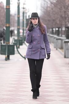 Giovane donna alla moda in cappello e cappotto di autunno che cammina lungo la città