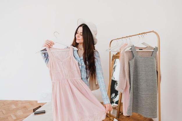 Elegante giovane donna in cappello e tailleur in boutique di moda durante lo shopping