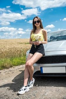 La giovane donna alla moda fa una pausa nel viaggio e riposa sul ciglio della strada vicino all'auto