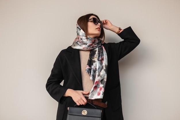 La giovane donna alla moda raddrizza gli occhiali da sole alla moda. modello di bella ragazza in sciarpa di seta sulla testa in cappotto elegante con borsa nera alla moda in pelle posa vicino al muro della città. signora di bellezza di affari.