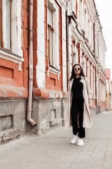 Elegante giovane donna in occhiali da sole vintage in abiti primaverili alla moda in scarpe bianche con borsetta passeggiate in città vicino al vecchio edificio. urbano bella ragazza hipster in abito casual alla moda viaggia per strada.