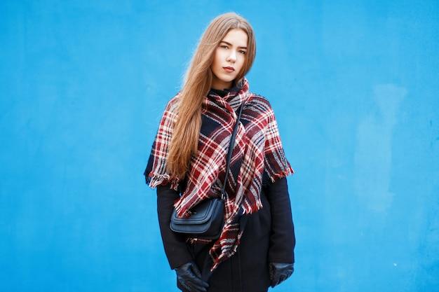 Elegante giovane donna con una sciarpa rossa a scacchi e cappotto invernale vicino al muro blu