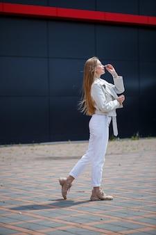 Elegante giovane donna con lunghi capelli biondi di aspetto europeo con un sorriso sul viso. ragazza con una giacca bianca e jeans bianchi una calda giornata di sole estivo sullo sfondo di un edificio grigio