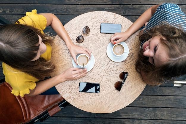 Giovani donne alla moda che hanno un incontro amichevole con tazze di caffè mentre sono sedute a tavola e chiacchierano