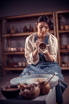 Elegante scultore artigiano lavora con l'argilla sulla ruota di un vasaio e al tavolo con gli strumenti