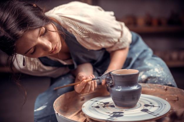 Elegante maestro artigiano che fa ceramiche, scultore di argilla bagnata su ruota