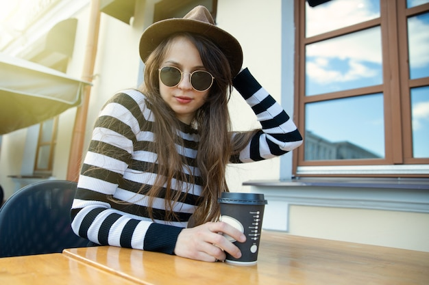 Giovane donna elegantemente vestita in un cappello e bicchieri beve caffè sulla terrazza di un bar