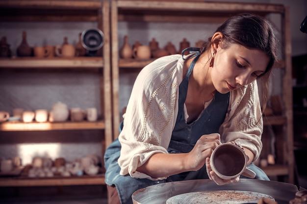 La scultrice studentessa stylishpotter lavora con l'argilla sulla ruota di un vasaio e al tavolo con gli strumenti. fatto a mano.