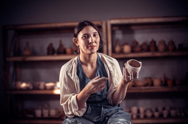 Elegante giovane e allegra donna che modella un vaso di argilla su un tornio da vasaio