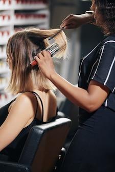 Stilista che spazzola i capelli del cliente