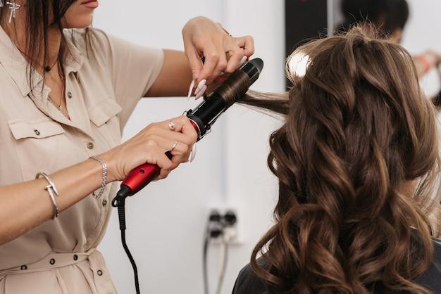 Lo stilista fa i riccioli ragazza di arricciatura con capelli marroni lunghi in un salone di bellezza professionale