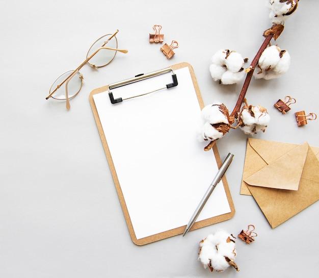 Appunti di accessori per ufficio disposti stilizzati, clip, occhiali, fiori di cotone, penna, vista dall'alto